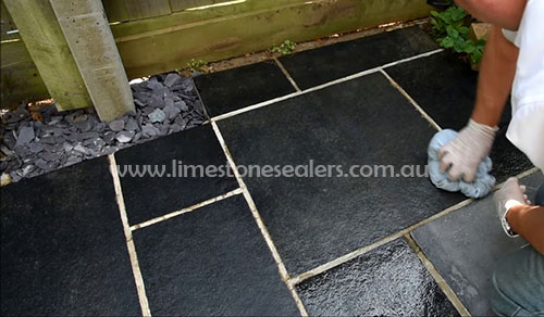 Sydney man cleaning and sealing black limestone